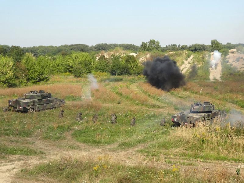 Die Panzergrenadiere sitzen ab, bilden eine Schützenreihe und nehmen den Kampf auf