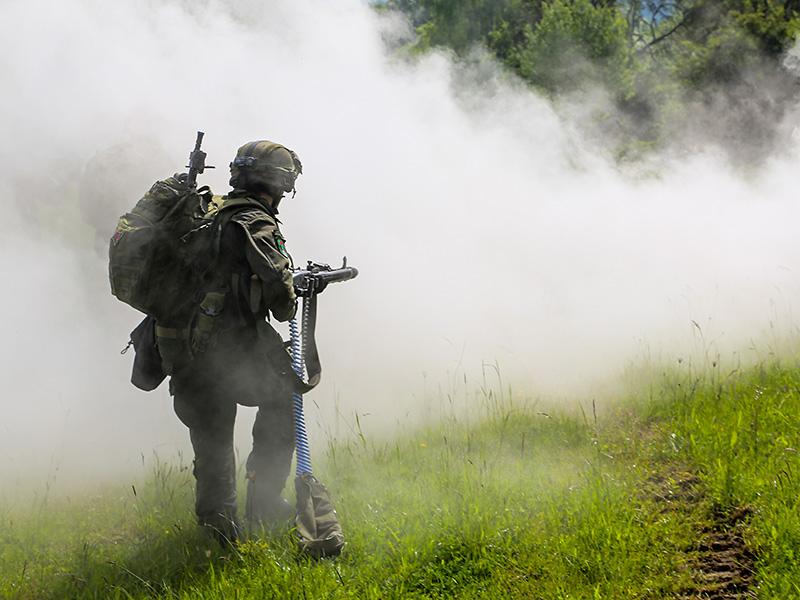 Österreichischer MG-74 Schütze rückt im Schutz von Rauchgranaten vor © US Army JMTC