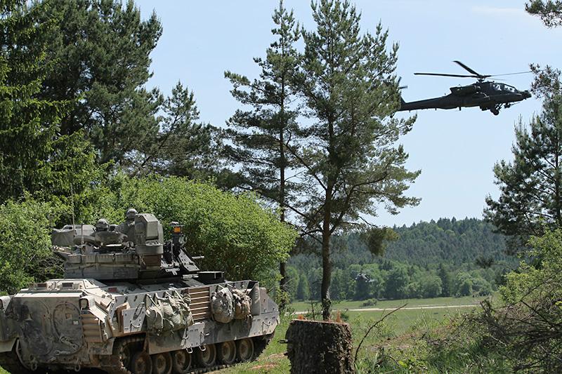 """Kurz drauf im Feld: Bradley Schützenpanzer werden von Apache Kampfhubschraubern gedeckt © US Army / Das in Grafenwöhr eingelagete """"European Activity Set"""" EAS rollt an. Hier Panzerhaubitzen M-109A6 Paladin © US Army - 1/1 CD"""
