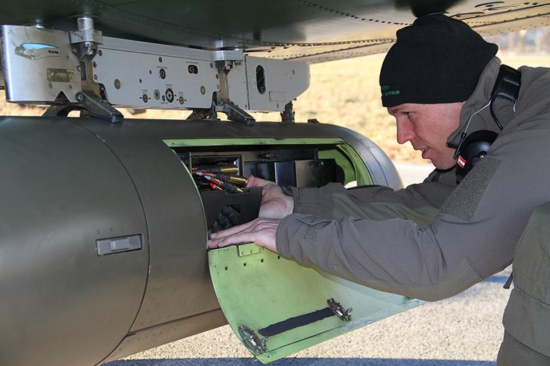 Ein Techniker prüft die HMP-250 Pods einer PC-7. Die rote Patrone ist Leuchtspurmunition © Bundesheer